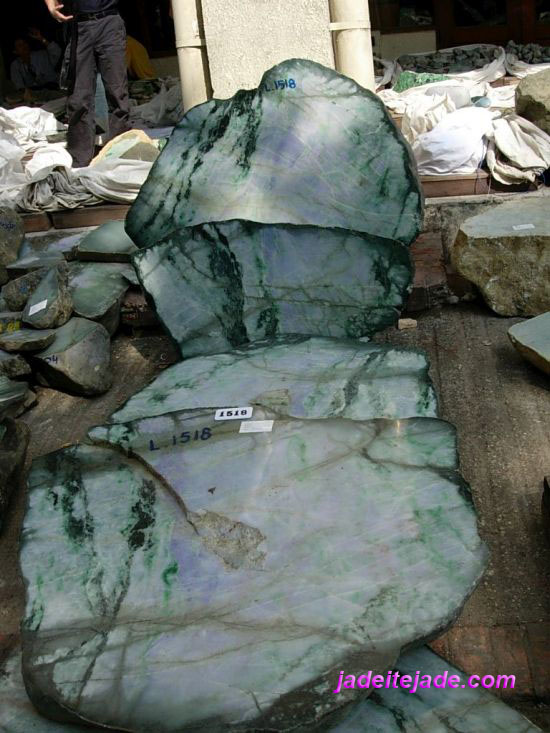 Natural fractures in jadeite jade boulder have dark green or brownish lines caused by oxidation