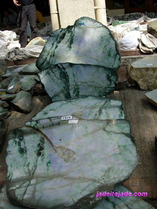 Natural fractures in jadeite jade boulder have dark green or brownish lines caused by oxidation